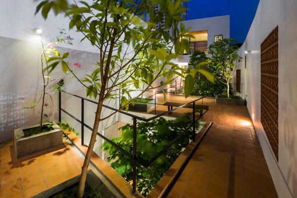 Giữa hai tòa nhà được nối bằng một hành lang. Cây xanh được trồng ở giữa.