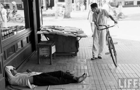 Người bán báo nằm ngủ cạnh sạp báo của mình. Ảnh: Life