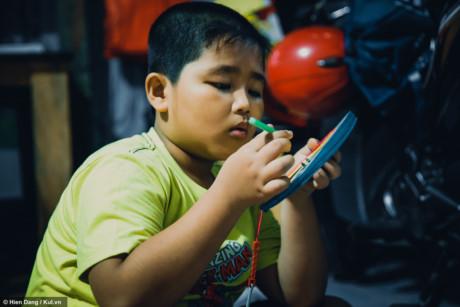 Em Lê Nguyễn Công Danh - 8 tuổi, vừa đi học về nhà là lật đật lôi lồng đèn, đèn cầy để chuẩn bị.