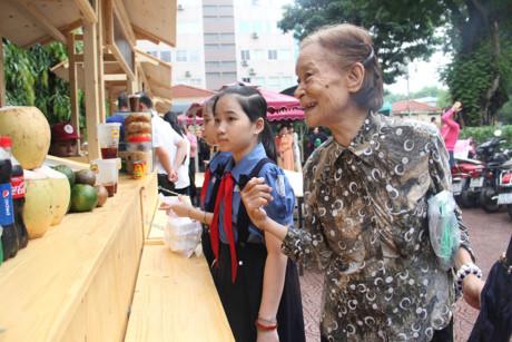 Nhiều người lớn, học sinh cùng ghé gian hàng phố hàng rong mua đồ ăn sáng. Ảnh: H.B.