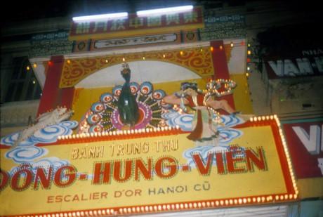 Em bé và chiếc đèn lồng hình chú chim ngộBảng hiệu của tiệm bánh Trung thu Đông Hưng Viên ở cửa Tây chợ Bến Thành, một thương hiệu có nguồn gốc từ phố Hàng Buồm ở Hà Nội. Ảnh: Douglas Ross.