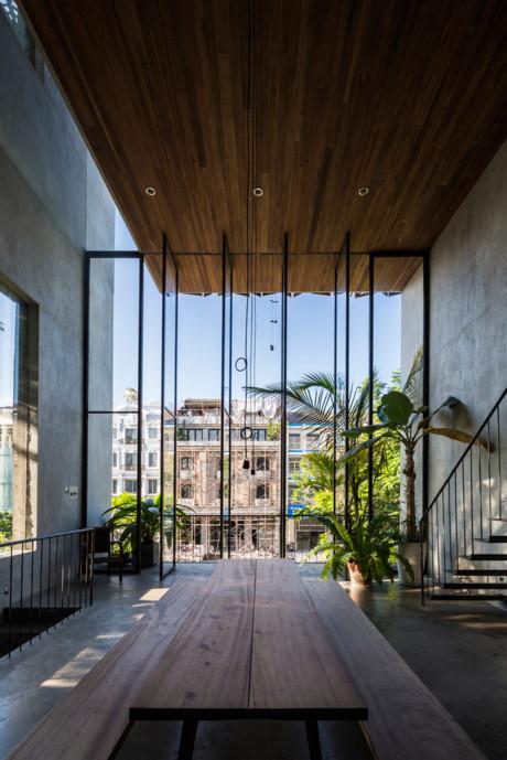 Không gian sống và khu vực ăn uống được mở rộng theo chiều dọc, cùng với bức tường kính lớn giúp hòa hợp không gian trong nhà với ngoài trời.