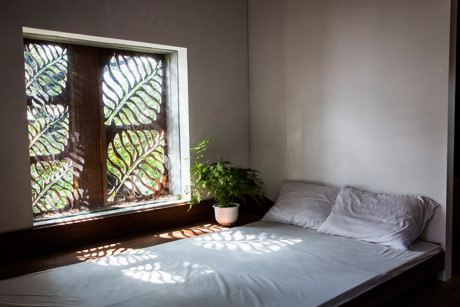 Giường ngủ bên cạnh cửa sổ đón nắng.