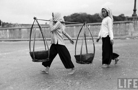 Những người phụ nữ chân trần đi bán rong khắp phố phường là hình ảnh quen thuộc ở Sài Gòn xưa. Ảnh: Life.