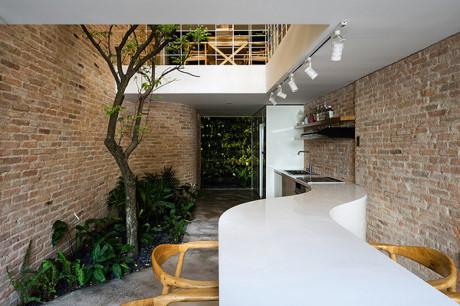 Phía bên trong tầng 1 là khu vực bếp với tông trắng chủ đạo và tràn ngập cây xanh.