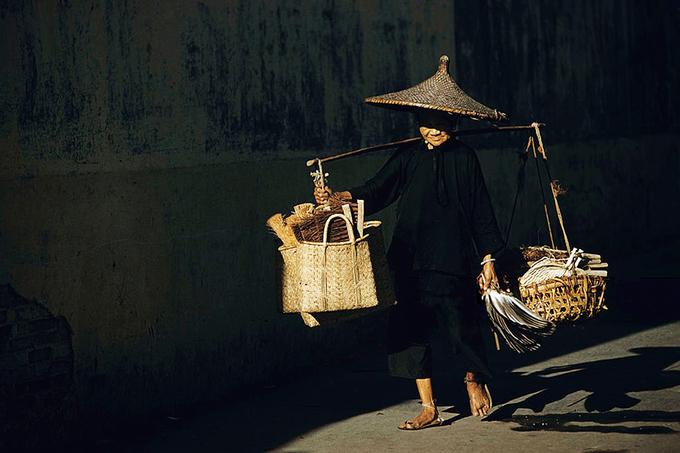 Một cụ bà với chiếc gánh bàn chải, chổi và quạt trên vai.