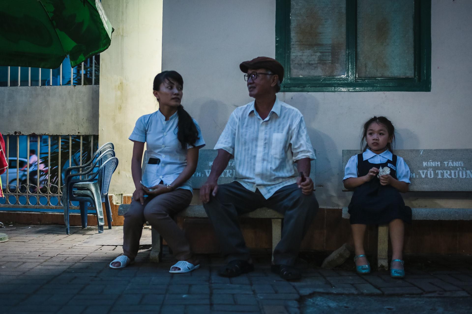 Hai ông cháu ngồi chờ trong ghế đá tại sân trường.