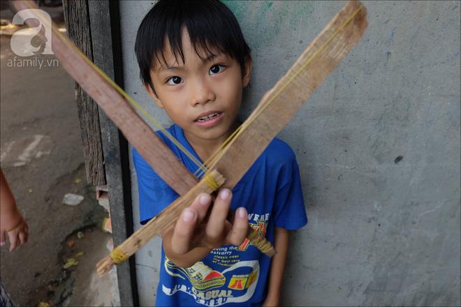 Em An (10 tuổi) khoe cây súng gỗ của mình vừa mới chế tạo được.