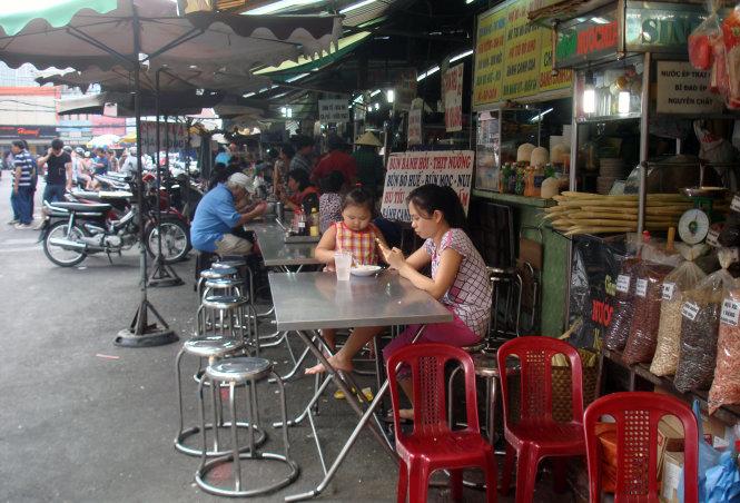 """ạn Nguyễn Trọng Minh: """"Ở miền Bắc vào, tôi thú vị nhất là các quán ăn vỉa hè khu trung tâm TP.HCM rất sạch sẽ, gọn ghẽ và giá cả không hề phân biệt người ở đâu, trong hay ngoài nước đều giá như nhau"""" - Trong ảnh dãy quán vỉa hè bên hông chợ Tân Định, một chợ Sài Gòn xưa trưa 12-12 - Ảnh: M.C"""