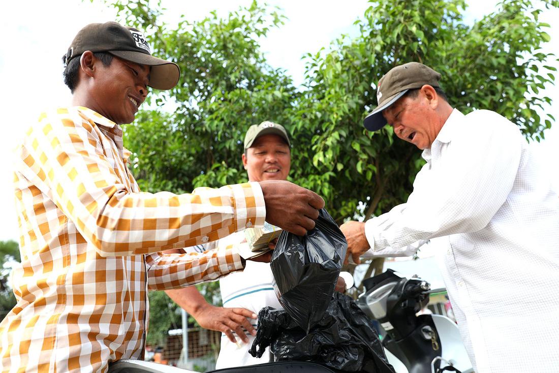 Nét đặc biệt của chợ bò là sử dụng tiền của nước bạn Campuchia để thanh toán - Ảnh: HỮU KHOA