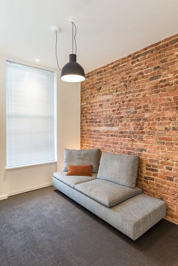 Bức tường gạch được sử dụng để tăng sự ấm áp, độ chắc chắn trong kết cấu và màu sắc sáng cho không gian sống. Nó tương phản với phần còn lại của đồ trang trí như sopha, thảm trong phòng khách này.