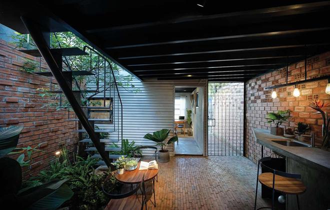 Bước vào khu vực sinh hoạt chung, bạn rất dễ có cảm giác thân quen bởi hệ cây xanh trồng đan xen trong nhà, dưới những giếng trời được tính toán kĩ để lấy sáng cho căn nhà ống. Song song với đó, những bức tường gạch mộc cũng đem lại hiệu quả thị giác và thẩm mỹ cao.