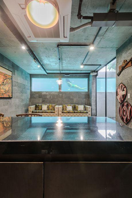 Không gian dưới tầng hầm sử dụng những cửa kính lớn, khi ngồi tại đây người trong phòng có thể nhìn thẳng ra bể bơi và ngắm nhìn mọi người bơi lội, tiệc tùng.