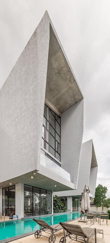 Toàn bộ ngôi nhà toát lên vẻ đẹp khoáng đạt, rộng mở mang đến cảm giác thoải mái. Các đường nét thiết kế sắc cạnh và mạnh mẽ, kết hợp giữa bê tông, gỗ, vật liệu kính và cây xanh vô cùng độc đáo.