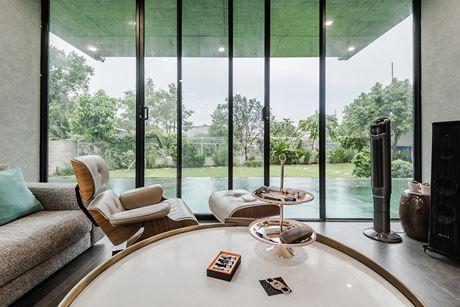 Tầng 1 của căn nhà là khu vực phòng khách với phần nội thất sang trọng và đơn giản. Hệ thống cửa trượt bằng kính mở trực tiếp ra bể bơi. Chỉ cần mở cửa bạn sẽ cảm nhận được ngay làn không khí trong lành và mặt đất mát mẻ ngay bên dưới.