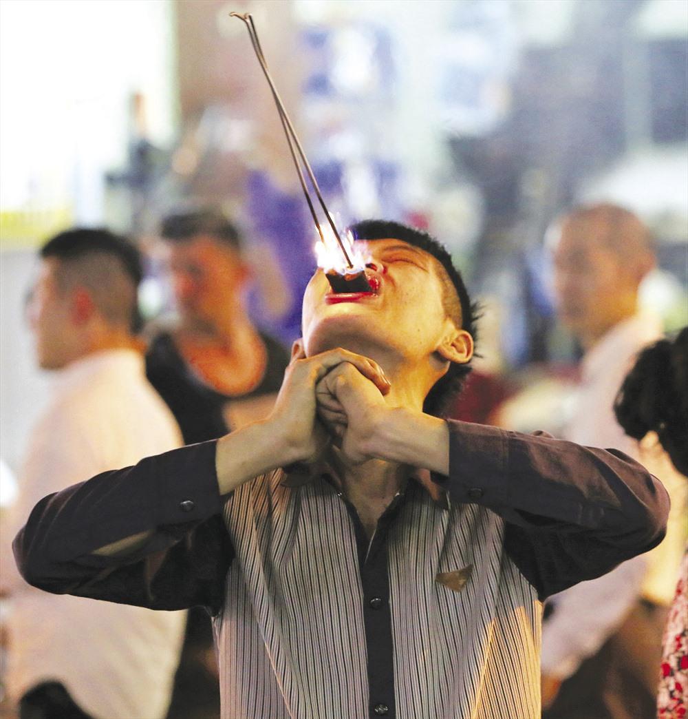 Trong ảnh là một thanh niên đang mưu sinh bằng nghề nuốt lửa, dao lam trên đường Bùi Viện. Công việc của anh là trình diễn màn nuốt lửa và nhai nát một con dao lam. Để thu hút sự chú ý của khách, trước khi trình diễn, anh thường hô lớn một hoặc vài tiếng, khi nào thấy nhiều người chú ý vào mình thì anh mới trình diễn.