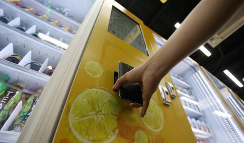 Đưa màn hình điện thoại vào máy bán hàng quét mã vạch ứng dụng mua sản phẩm