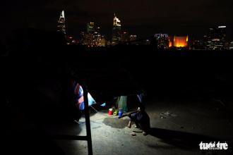 Ông Dương Đình Thống (49 tuổi, quê Thanh Hóa) ngồi trước căn lều nhỏ như cái chuồng gà canh giữ máy cẩu tại một công trình ở Thủ Thiêm - Ảnh: HỮU KHOA