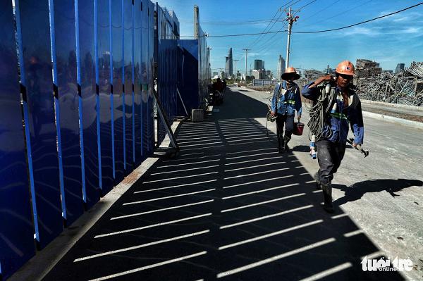 Công nhân trên đường về lán trại sau một ngày vất vả trên công trường - Ảnh: HỮU KHOA
