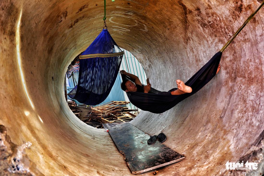 Anh Thái Văn Minh mắc võng nằm nghỉ trong một ống cống công trình vì nắng lên lán trại rất nóng - Ảnh: HỮU KHOA