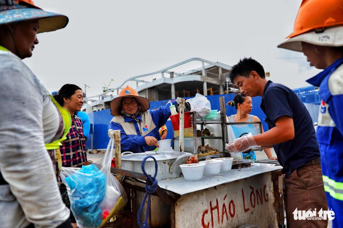 Để tiết kiệm tiền, nhiều công nhân ăn cháu lòng thay cơm với giá 10.000đ/tô bán tại công trường- Ảnh: HỮU KHOA