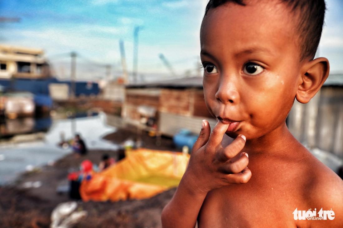 Nhiều đứa trẻ không được đi học khi theo cha mẹ ở tại các lán trại công trường - Ảnh: HỮU KHOA