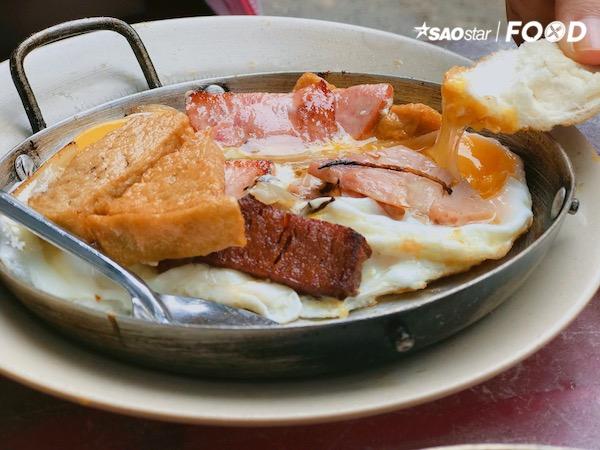 Bạn nên gọi một phần thập cẩm để có thể hài hoà và kết hợp từng tầng vị giác. Chiếc chảo thiếc nóng hổi đầy ắp cùng trứng ốp la, chả cá, chả lụa, jambon và pate gan trông vô cùng hấp dẫn. Đừng quên dặn trứng đừng chín quá nhé, như thế mới có thể cảm nhận được vị béo thơm của món ăn