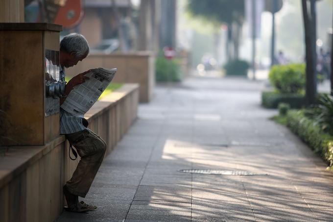 """Người đàn ông đọc báo trên đường Hai Bà Trưng (quận 1). """"Sương mù như vầy thật ra không hiếm ở Sài Gòn, nhưng dày đặc như hôm nay thì rất ít. Trời mát mẻ, tự nhiên thấy cuộc sống như chậm lại"""", ông chia sẻ."""