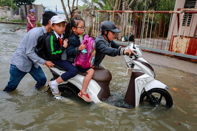 """Đưa hai con đi học qua đường Lê Văn Lương nhưng xe chết máy giữa biển nước, anh Long (40 tuổi) bảo các con ngồi yên vì không muốn chúng xuống đường ướt quần áo. Hì hục đẩy xe lên vỉa hè sửa chữa nhưng không thể, anh phải nhờ người đi đường hỗ trợ. """"Từ nhà đến trường con tôi khoảng 4-5 km. Bữa nay triều cường lên cao quá, mong xe mau chạy được chứ không sẽ trễ giờ học của tụi nhỏ"""", anh nói, vẻ lo lắng."""