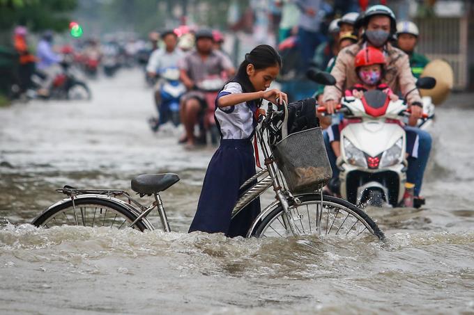 Bé Phương (học sinh THCS Nguyễn Văn Quý) tỏ ra lúng túng khi sóng nước liên tục đẩy xe đạp ngả nghiêng.