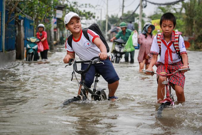 Học sinh trường tiểu học Lê Lợi gồng mình đạp xe qua đoạn đường ngập sâu.
