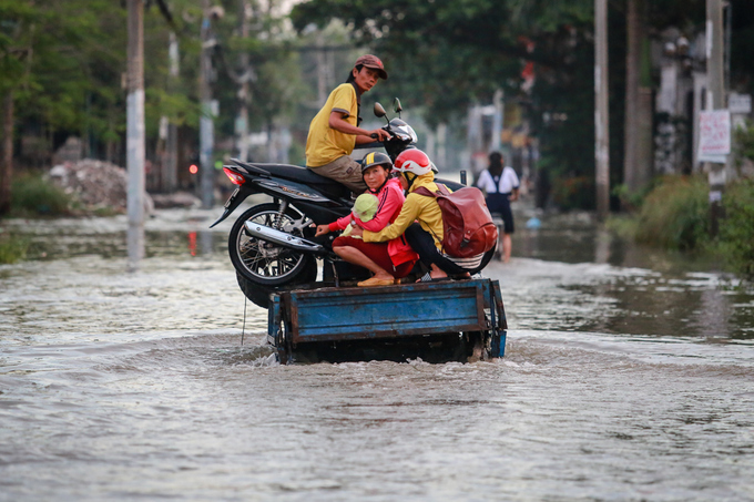 Gia đình anh Hùng phải thuê xe ba gác với giá 50.000 đồng đưa qua đoạn đường ngập dài 3 km.