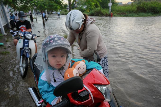 Tương tự, mẹ con bé Mai Hoa (3 tuổi, huyện Nhà Bè) và nhiều người bị kẹt giữa dòng nước vì xe hỏng.
