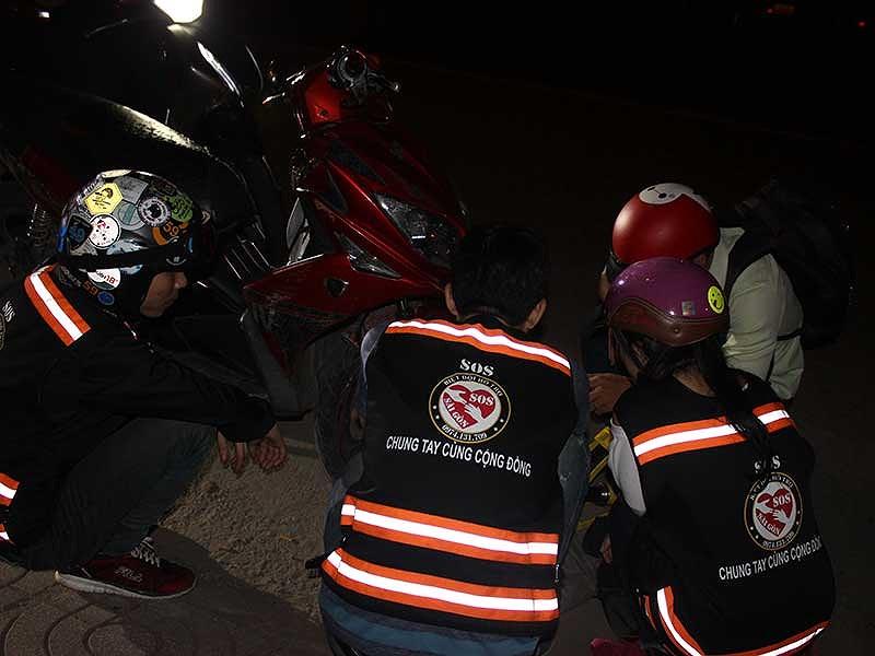 Đội SOS Sài Gòn ra tay vá xe cho một trường hợp bể bánh giữa đường. Ảnh: H.LAN