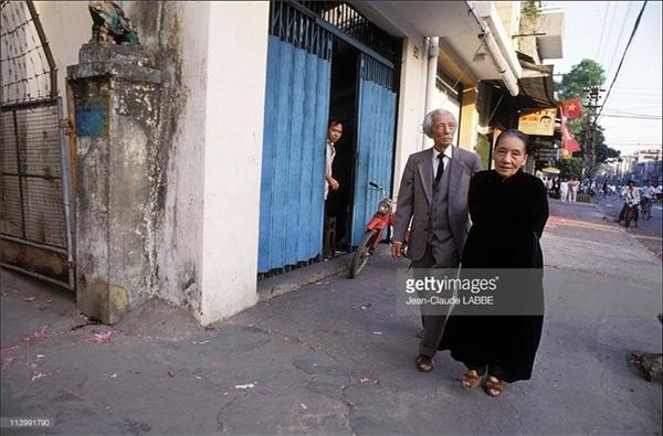 Hai cụ già ung dung đi ngắm phố phường Sài Gòn.