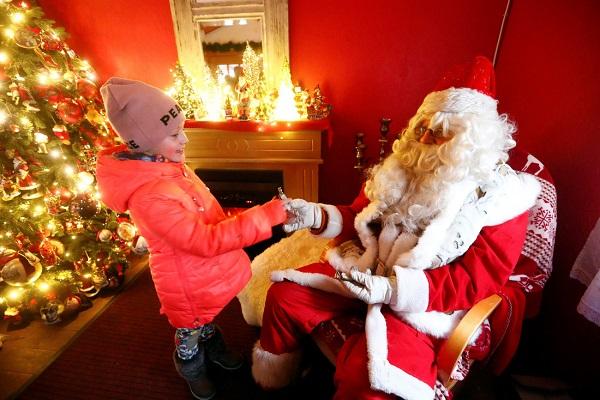 Ông già Noel phát quà cho một bé gái ở Estonia - Ảnh: REUTERS