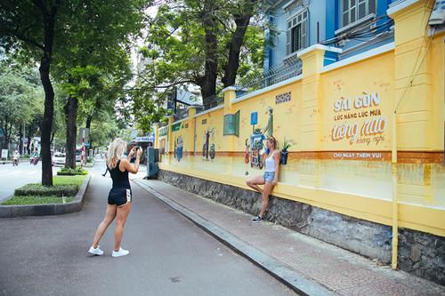 """Hai nữ du khách đầy phấn khích ngắm nhìn những hình ảnh những """"Món ngon Sài Gòn"""" được tái hiện trên mảng tường lớn trước cổng Phòng Công chứng số 1 (Pasteur, Q.1) trước khi cùng chụp lại những hình ảnh đẹp cho chuyến du lịch của mình."""