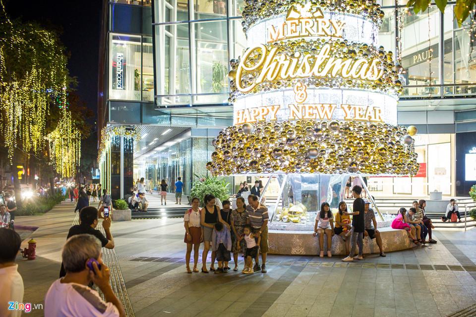 Các gia đình đi chơi Noel sớm và chụp ảnh với họa tiết trang trí ở trung tâm thương mại.