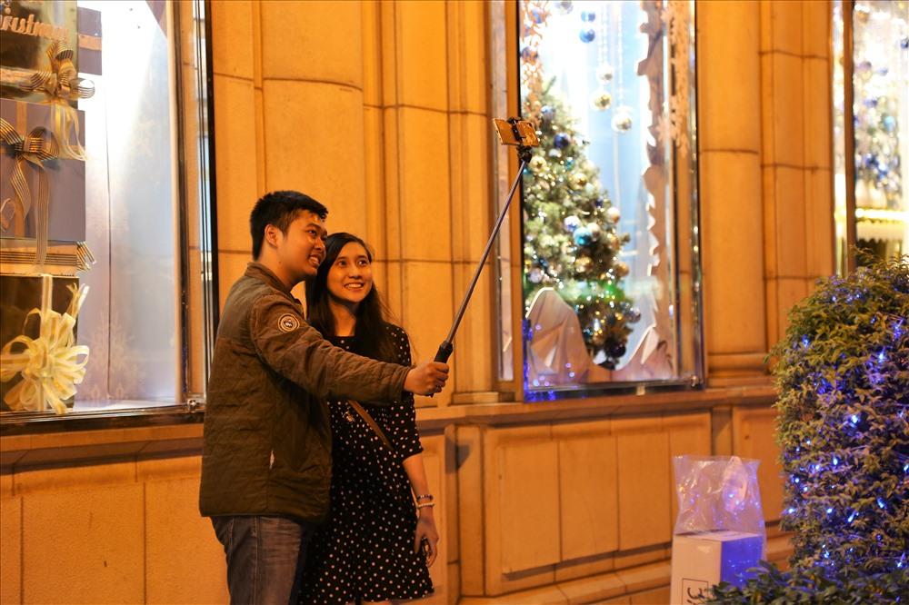 Đôi bạn trẻ trang thủ chụp hình lưu niệm trước một tòa nhà được trang trí rực rỡ dịp Giáng sinh. Ảnh: Trường Sơn