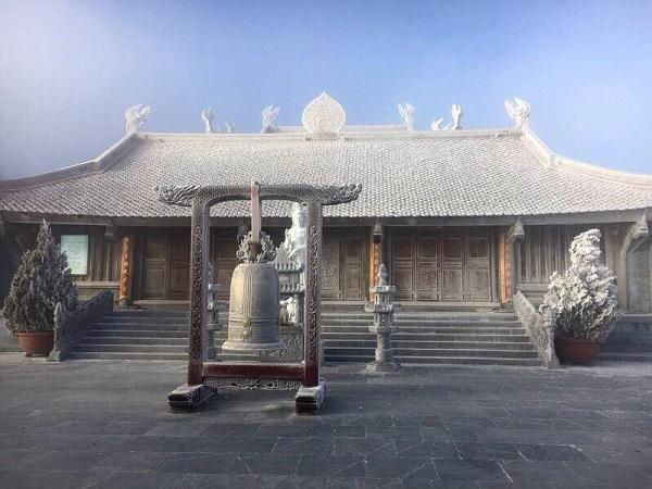 Gác chuông và ngôi chùa trên đỉnh núi bị phủ một màu trắng xóa