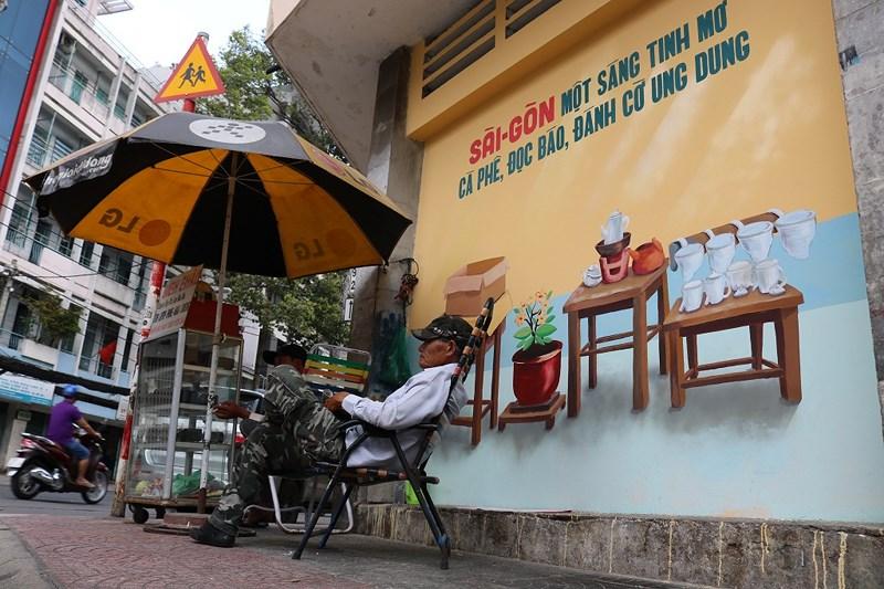 """""""Sài Gòn một sáng tinh mơ. Cà phê, đọc báo, đánh cờ ung dung"""" là một câu nói được viết lên bức tường... Hãy thử một lần nhé... Như ông bác trong hình này nè, mệt mỏi, muộn phiền gì tan biến hết. Ảnh: LA HIÊN"""