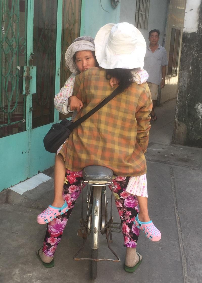 Hàng ngày, chị Trinh đều để con ngồi trên yên trước xe đạp và cùng đi bán vé số - Ảnh: Internet