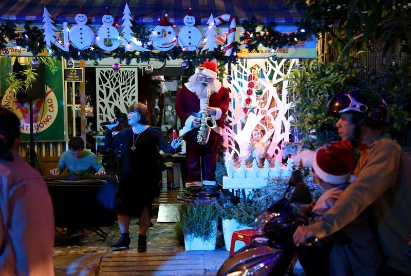 Mô hình ông già Noel hòa vào đêm nhạc sôi động của một gia đình vui Noel sớm trên đường Thành Công.