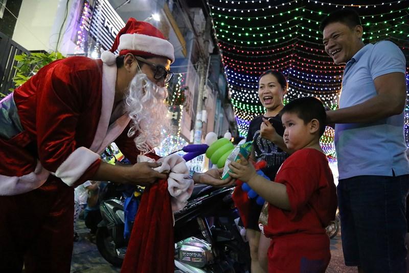 Em nhỏ bất nhờ nhận được quà của ông già Noel khi xuống phố dạo chơi.