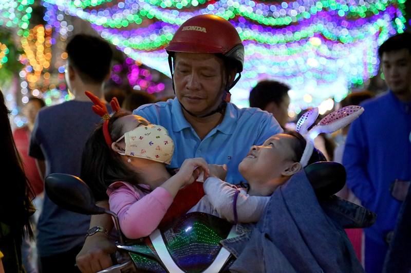"""Dù chưa đến Noel nhưng """"biển người"""" đã đổ về con đường đèn Thành Công (quận Tân Phú) và một số đường lân cận để vui chơi, check in chuẩn bị đón một mùa lễ Giáng sinh an lành. Trong ảnh: Hai em nhỏ đi chơi Noel đang ngồi trên xe để cố vượt qua """"biển người"""" ở đường đèn Thành Công."""
