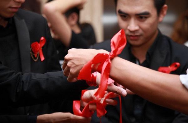 Bạn trẻ tham dự cùng buộc dải băng đỏ trên cổ tay, thể hiện ủng hộ đồng hành cùng những người nhiễm HIV tại lễ trao giải Dải băng đỏ, dành cho những người có cống hiến cho phong trào phòng chống HIV ở Việt Nam, tổ chức tại TP. HCM ngày 1-12-2017 - Ảnh: PHONG NGUYỄN