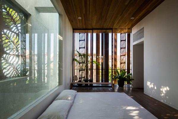 Phòng ngủ ngập ánh sáng có điểm nhấn là cửa gỗ xoay họa tiết lá.