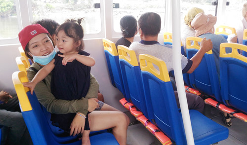 Một em bé háo hức khi được mẹ dẫn đi buýt đường thủy