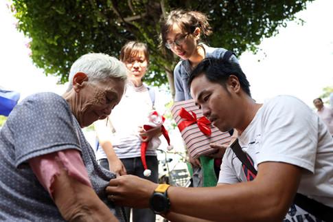 Cụ Trần Thị Kim Dung (79 tuổi, Q.1) được các bạn tình nguyện viên chỉn lại áo để chụp ảnh