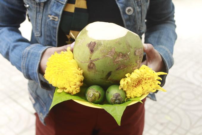 Trước miếu, vài người bày bán đĩa lễ gồm dừa, trầu cau và hoa cúc cho các quý cô đi lễ năm Mẹ, cầu duyên lành.